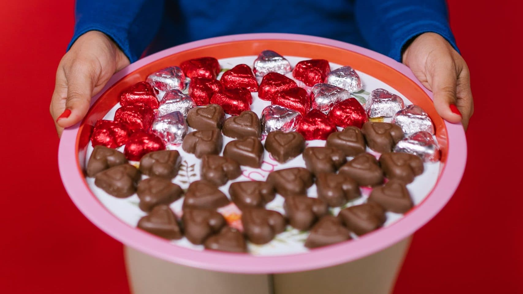 photo of person holding tray of heart shaped chocolates