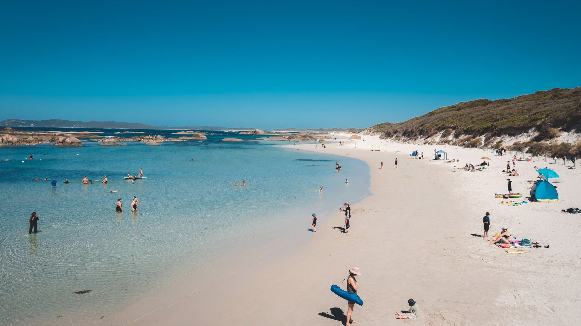 sandy beach with many people in sunny summer weather